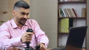 Volwassen mens die tijd verspillen bij werk, die schuttervideospelletjes met bedieningshendel het spelen stock videobeelden