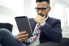 Volwassen mens in een jasje en glazenvaardigheden in recentste media die strategieën op de markt brengen die in het coworking van royalty-vrije stock foto's