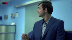 Volwassen mens in formele slijtagezitting in de gang in moderne privé kliniek die op zijn kaartje van de draaiholding ter beschik stock videobeelden