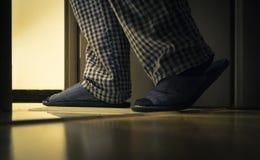 Volwassen mens in pijamasgangen aan een badkamers bij de nacht Het concept van mensen` s healths stock afbeeldingen