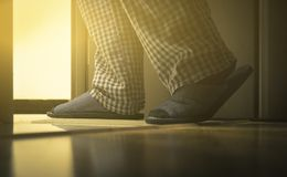 Volwassen mens in pijamasgangen aan een badkamers bij de nacht Het concept van mensen` s healths gestemd Stock Afbeelding