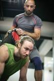 Volwassen mensen die gewichtheffen in gymnastiek doen Stock Afbeelding