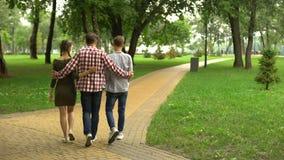 Volwassen met dochter en zoon in park lopen, en vader die, familie koesteren spreken stock videobeelden