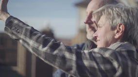Volwassen paar dat zich in openlucht bevindt Rijp echtpaar die in de zon communiceren Familieverhoudingen stock footage