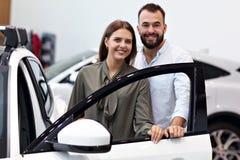 Volwassen paar die nieuwe auto in toonzaal kiezen royalty-vrije stock foto's