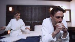 Volwassen paar die in witte badjassen in hotelruimte debatteren De vrouw schreeuwt bij de haar mens stock video