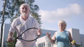 Volwassen paar speeltennis op een zonnige dag Een oude man en een rijpe vrouw genieten van het spel Recreatie en Vrije tijd stock footage