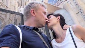 Volwassen paaromhelzing en kus elkaar in een stadskerk stock videobeelden