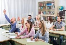 Volwassen studenten met handen omhoog bij klasse Stock Foto's