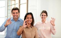Volwassen uitvoerend team met o.k. vingersteken stock afbeeldingen