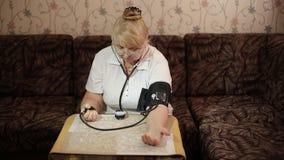 Volwassen vrouw die bloeddruk meten Gezondheidszorg in volwassenheid stock videobeelden