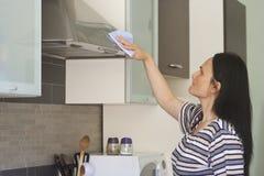 Volwassen vrouw die de keukenkap schoonmaken Royalty-vrije Stock Fotografie