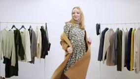 Volwassen vrouw die een laag en een hoed uitstellen terwijl het dansen in een kledingsruimte stock videobeelden