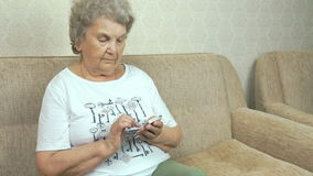 Volwassen vrouw die een mobiele telefoon thuis houden stock footage