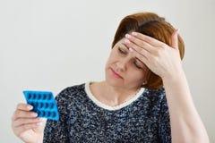 Volwassen vrouw die een pil voor hoofdpijn nemen stock fotografie