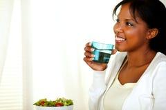Volwassen vrouw die en zoet water glimlacht drinkt Stock Foto's