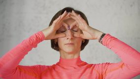 Volwassen vrouw die glazen tonen door handen terwijl de voorcamera van de gezichtsmassage Sluit omhoog vrouw die de massage van h stock videobeelden