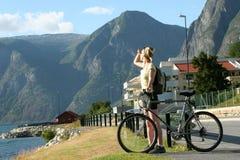 Volwassen vrouw die met fiets de bergen bekijkt royalty-vrije stock foto