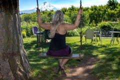 Volwassen vrouw die op een houten boomschommeling slingeren in MT kap Oregon Concept voor kinderlijk geluk, onschuld, pret royalty-vrije stock fotografie