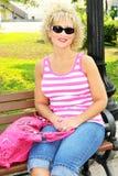 Volwassen vrouw die op een parkbank situeert met roze beurs Royalty-vrije Stock Afbeeldingen