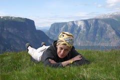 Volwassen vrouw die op het gras bij de bovenkant van berg ligt royalty-vrije stock afbeeldingen