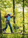 Volwassen vrouw in een helm en met een veiligheidssysteem die voorzichtig op hangbrug op de achtergrond van bomen lopen royalty-vrije stock afbeeldingen