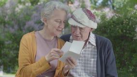 Volwassen vrouw en man die oude foto's die gelukkige ogenblikken herinneren die op een bank in het park zitten kijken Rijp paar i stock video