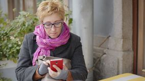 Volwassen vrouw met koffie en smartphone stock footage