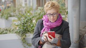 Volwassen vrouw met koffie en smartphone stock videobeelden