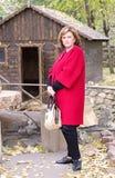 Volwassen vrouw in rode laag die zich in het de herfstpark bevinden royalty-vrije stock foto