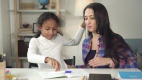 Volwassen vrouw in schoolklasse zitting en het smilling samen met haar jonge studente gelukkig voor het tonen van academische res stock video