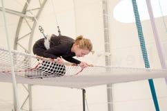Volwassen vrouwelijk land op netto, voorbereidingen treffend om bij a op een vliegende trapezeschool bij een binnengymnastiek te  stock fotografie