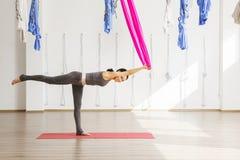 Volwassen vrouwenpraktijken die positie van de stok anti-gravity yoga in studio in evenwicht brengen Stock Foto