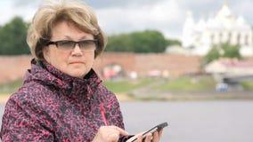 Volwassen vrouwentoerist die een smartphone in openlucht houden stock footage
