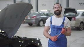 Volwassen werktuigkundige die zich dichtbij de auto met een open kap bevindt en reusachtige moersleutel in handen houdt Gebaarde  stock footage