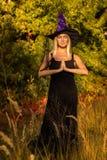 Volwassen wijfje in heksenkostuum het praktizeren yoga Stock Foto