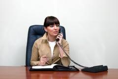 Volwassen witte vrouw achter een bureau in een bureau dat spreekt royalty-vrije stock foto's