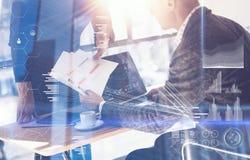 Volwassen zakenman die moderne laptop werken en documenten tonen aan jonge collega Virtueel concept het digitale scherm, stock afbeelding