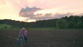Volwassen zoon die met zijn oude vader op grondgebied lopen, mooie mening van gecultiveerd land tijdens zonsondergang op achtergr stock footage