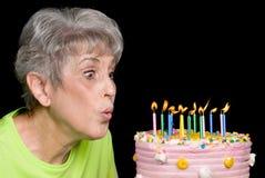 Volwassene die uit kaarsen blaast Stock Foto