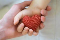 Volwassene en kindhanden die rood hart houden stock afbeeldingen