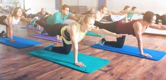 Volwassenen die yogaklasse in sportclub hebben stock afbeeldingen