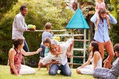 Volwassenen en jonge geitjes die pret het spelen in een tuin hebben royalty-vrije stock afbeeldingen