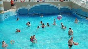 Volwassenen en kinderen die in waterpark rusten stock videobeelden