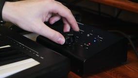 Volym och kompressor för hand för solid tekniker vändande upp, medan blanda och styra musik på den solida blandande hemmastadda i arkivfilmer