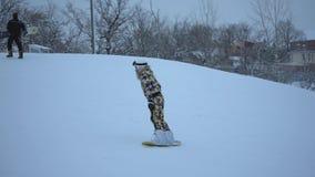 VOLZHSKII RYSSLAND - JANUARI 8, 2017: En flicka i en skidasemesterort i den speciala dräkten rullade på hans snowboard, vid henne stock video
