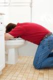 Vomitando nella toilette fotografia stock