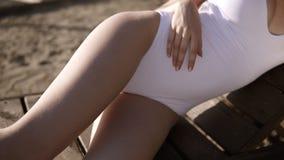 Von den Füßen zur Hauptansicht der jungen sinnlichen Frau in der stilvollen weißen Schwimmenklage, die auf Strandbank faulenzt Sc stock video footage
