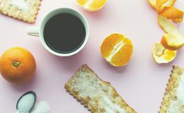 Von den oben genannten Bonbons, vom Tasse Kaffee und von den Früchten auf rosa Hintergrund lizenzfreies stockfoto