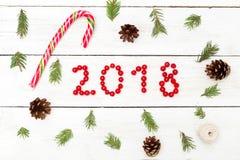 2018 von den roten Beeren und von der Weihnachtssüßigkeit auf einem hölzernen Hintergrund Lizenzfreies Stockfoto